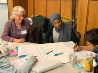 students and faculty work together at a table.